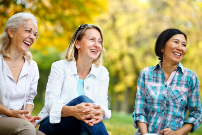 Three mature ladies outdoors enjoying and laughing