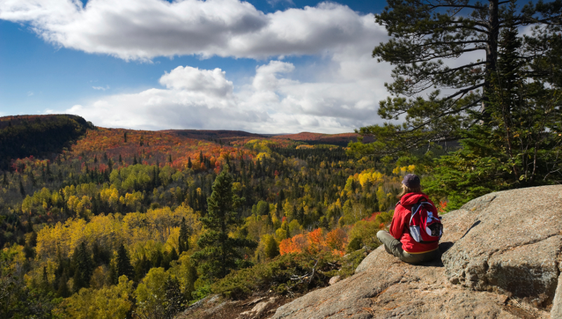Female hiker sitting on rocky ledge taking in a scenic Autumn view in Minnesota's Arrowhead region from Oberg Mountain.