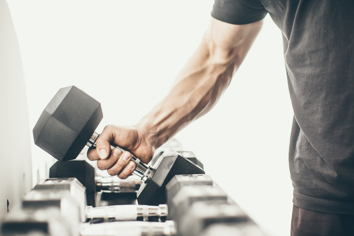 man taking dumbbells in a gym