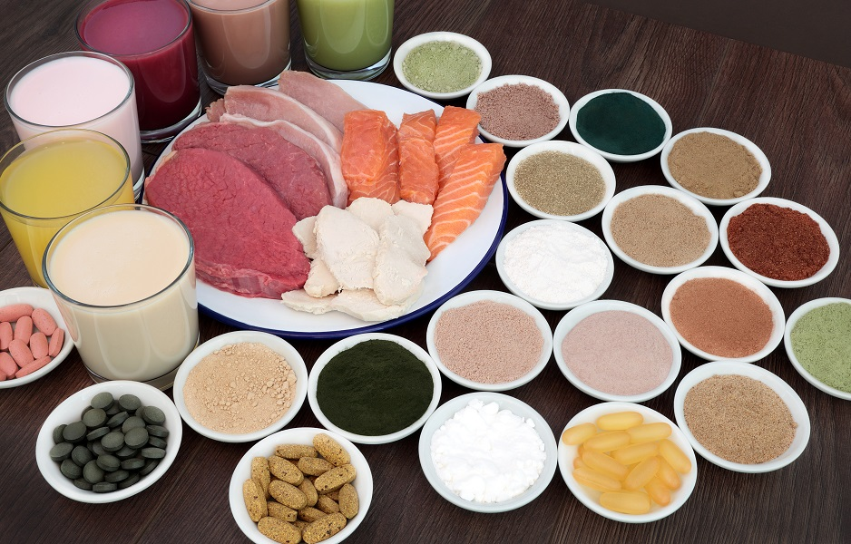 Health food and drinks for body builders with lean meat of steak, chicken and pork with salmon and dietary supplemment powders and vitamin pills on oak background.