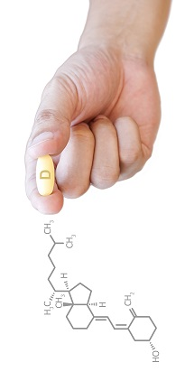 Hand holding vitamin D pill with clipping path