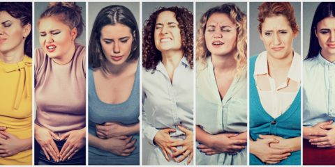 Group of women with hands on stomach having pain