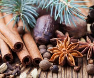 Christmas winter spices on wooden background.