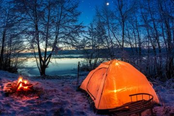 Sunrise on winter lake covered with snow at dusk